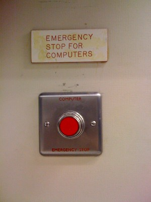 Red push button on the wall labeled, Emergency Stop for Computers